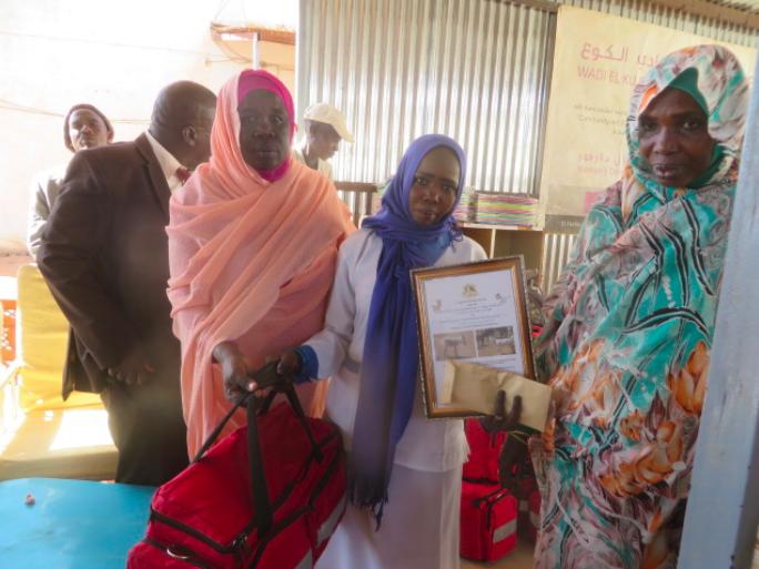 Munira receiving certificate and midwifery kit